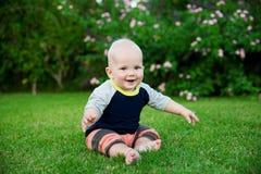 De gelukkige aanbiddelijke zitting van de babyjongen op het gras Stock Afbeelding