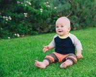 De gelukkige aanbiddelijke zitting van de babyjongen op het gras Stock Foto's