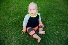 De gelukkige aanbiddelijke zitting van de babyjongen op het gras Royalty-vrije Stock Afbeeldingen