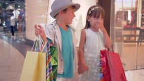 De gelukkige aankopen, klantenjonge geitjes met pakketten in handen genieten van winkelend gaan voorbij winkelvensters tijdens se stock footage