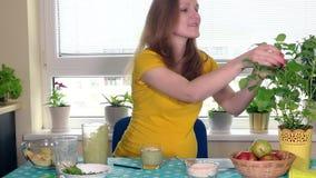 De gelukkige aanstaande moeder bereidt fruitcocktail voor en drinkt het die camera bekijken stock video