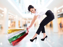 De gelukkige aantrekkelijke vrouw sleept het winkelen zakken. Royalty-vrije Stock Foto's