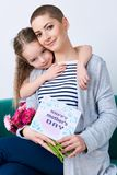 De gelukkige achtergrond van de moeder` s dag Leuk meisje die mamma na het geven van haar kaart van de moedersdag koesteren royalty-vrije stock foto