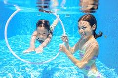 De gelukkige actieve jonge geitjes zwemmen in pool en spelen onderwater Royalty-vrije Stock Foto