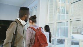 De gelukkige Afrikaanse Amerikaanse mannelijke student loopt in universitaire gang stotende schouder van schaamteloze hipsterkere stock videobeelden