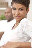 De gelukkige Afrikaanse Amerikaanse Zitting van de Vrouw thuis Royalty-vrije Stock Afbeeldingen