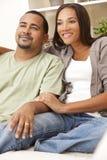 De gelukkige Afrikaanse Amerikaanse Zitting van het Paar thuis Stock Foto's