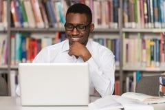 De gelukkige Afrikaanse Mannelijke Bibliotheek van Studentenwith laptop in Stock Afbeeldingen