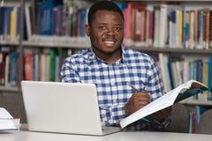 De gelukkige Afrikaanse Mannelijke Bibliotheek van Studentenwith laptop in stock foto's