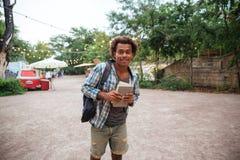 De gelukkige Afrikaanse rugzak en de boeken van de jonge mensenholding Stock Fotografie