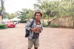 De gelukkige Afrikaanse rugzak en de boeken van de jonge mensenholding Stock Afbeelding