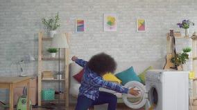 De gelukkige Afrikaanse vrouw met een afrokapsel werpt vuile kleren in de wasmachine zoals een bal in mand langzame mo stock footage