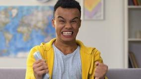 De gelukkige afro Amerikaanse jongen die voor favoriet team winnende sporten toejuichen past op TV aan stock videobeelden