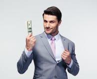 De gelukkige Amerikaanse dollars van de zakenmanholding Royalty-vrije Stock Foto's