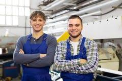 De gelukkige arbeiders bij de moderne industrie planten Royalty-vrije Stock Foto's