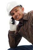 De gelukkige arbeiders glimlachen wanneer bespreking op mobiele telefoon Royalty-vrije Stock Afbeelding