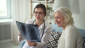 De gelukkige artsen bezoekende oudere dame en bespreekt röntgenstraal stock footage