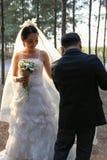 De gelukkige Aziatische bruidegom helpt omhoog zijn bruidkleding op een pijnboom bosachtergrond Stock Foto