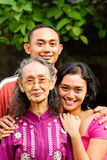 De gelukkige Aziatische jonge man en de vrouw omhelzen oude moeder royalty-vrije stock foto