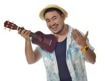 De gelukkige Aziatische mens nodigt uit om Ukelele te spelen isoleert achtergrond Stock Foto