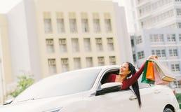 De gelukkige Aziatische toeristenvrouw heft het winkelen zakken op moderne witte auto op, bekijkt omhoog exemplaarruimte De activ stock foto