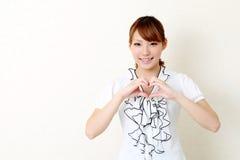 De gelukkige Aziatische vrouw maakt hartvorm door haar handen Royalty-vrije Stock Afbeelding