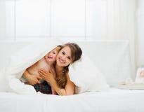 De gelukkige baby die van het moederbed uit van deken kijkt Stock Afbeeldingen