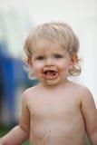 De gelukkige baby met een vuil gezicht na eet chocolade Royalty-vrije Stock Foto