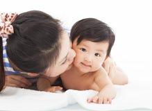 De gelukkige baby van het moeder kussende glimlachende kind Royalty-vrije Stock Afbeeldingen