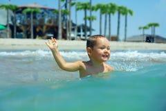 De gelukkige babyjongen geniet van zwemmend in overzeese golven Stock Foto