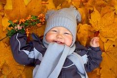 De gelukkige babyjongen ligt onder gevallen bladeren Royalty-vrije Stock Afbeeldingen