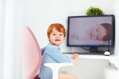 De gelukkige de babyjongen van de roodharigepeuter zit als bureauvoorzitter op werkende plaats Stock Fotografie