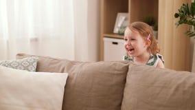 De gelukkige babymeisje het spelen huid - en - zoekt thuis spel stock videobeelden