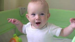 De gelukkige babyzitting in de glimlachende en bewegende handen van de babyvoederbak, blauwe ogen ziet eruit stock videobeelden
