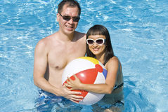 De gelukkige Bal van het Strand van de Holding van het Paar in een Zwembad Stock Afbeelding