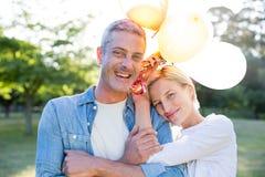 De gelukkige ballons van de paarholding bij het park Royalty-vrije Stock Foto's