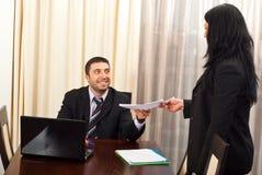 De gelukkige bedrijfsmens geeft documenten aan secretaresse royalty-vrije stock afbeelding