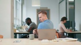 De gelukkige bedrijfsmens geniet van goed nieuws op kantoor Freelance mens die bij het coworking springen stock video