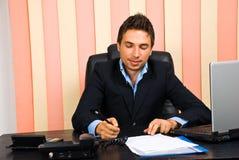 De gelukkige bedrijfsmens schrijft op papier in bureau Royalty-vrije Stock Afbeelding