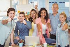 De gelukkige bedrijfsmensen met technologieën het tonen beduimelen omhoog royalty-vrije stock foto