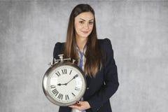 De gelukkige bedrijfsvrouw toont een klok Royalty-vrije Stock Fotografie