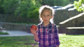 De gelukkige beten van weinig blondemeisje en grappig kauwen rijpe sappige appel in backlight, kijkt het jong geitje geklede over stock video