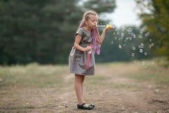 De gelukkige blazende zeepbels van het kindmeisje op gang in park royalty-vrije stock foto