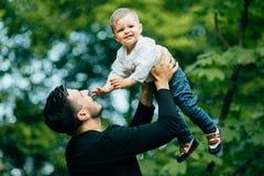 De gelukkige blije vader die pret hebben werpt in de lucht omhoog zijn klein kind, Royalty-vrije Stock Fotografie