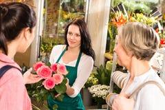 De gelukkige bloemistvrouw die rozen tonen bloeit klanten Royalty-vrije Stock Foto's