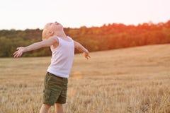 De gelukkige blonde jongen bevindt zich apart met zijn wapens en hoofd omhoog op een gemaaid tarwegebied De tijd van de zonsonder royalty-vrije stock afbeelding