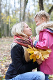 De gelukkige blondemoeder met esdoornpamfletten bekijkt dochter royalty-vrije stock afbeelding