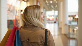 De gelukkige blondevrouw glimlacht en kijkt over haar schouder lopend met het winkelen zakken rond de wandelgalerij stock footage
