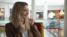 De gelukkige blondevrouw spreekt op de telefoon die zich met het winkelen zakken in de wandelgalerij bevinden stock footage