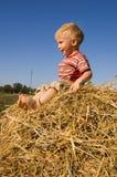 De gelukkige blootvoetse babyjongen zit op een hooiberg Royalty-vrije Stock Foto